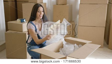 Smiling happy woman packing up her home