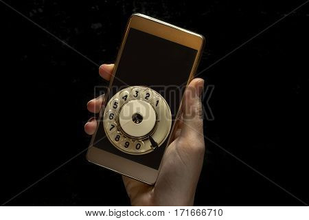 Hand holds mobile phone on a dark black background. The disc for dialing from the retro phone and copy space for writing your text and number. Conceptual photo.