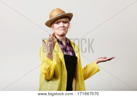 Suprised shocked woman gardener in sun hat and yellow raincoat waiting for rain gesturing with hands making funny face