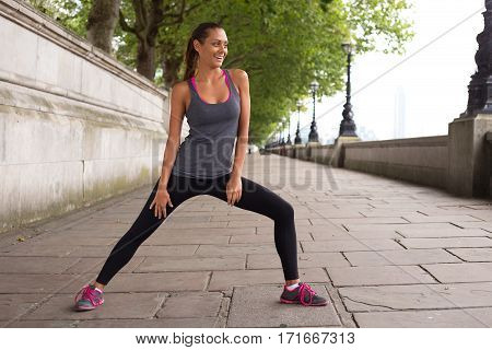 a fitness woman stretching along the river