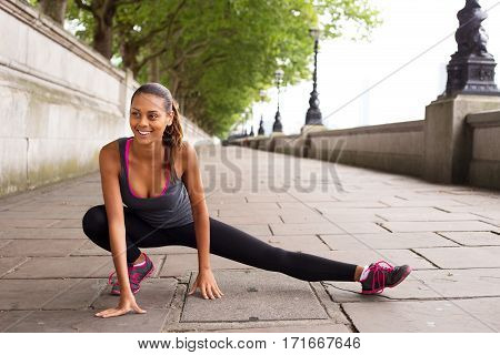 fitness woman stretching her leg muscles before going running