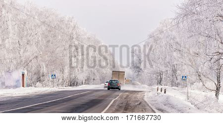 Cars on winter road with snow. Dangerous automobile traffic in bad weather.
