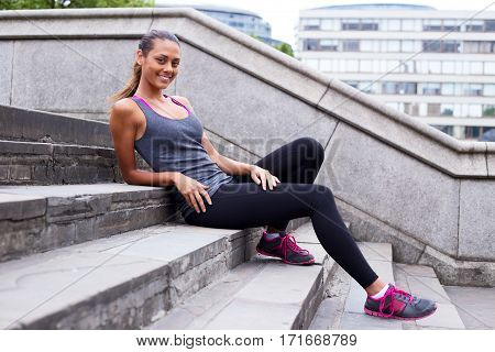 a beautiful fitness girl relaxing sitting on steps