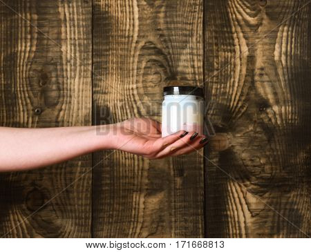 glass or plastic jar with lotion cream or bath salt white color for spa salon as health care in female hand on textured wooden background copy space