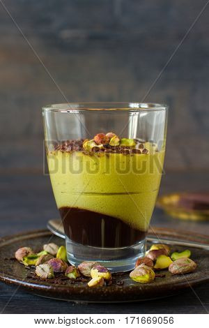 Elegant oriental dessert in a glass, pistachio mousse with chocolate