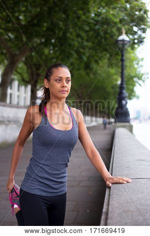 young woman stretching her muscles while out running
