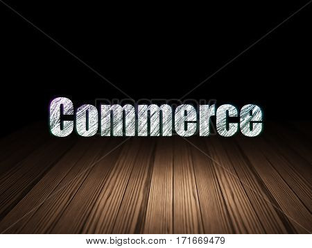 Finance concept: Glowing text Commerce in grunge dark room with Wooden Floor, black background