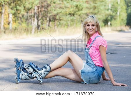 Young woman is sitting with rollers on the road. Happy woman is resting outdoors.