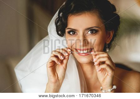 The smilling bride in white dress in the room