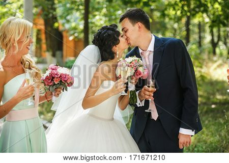 The bride and groom kissing in the park
