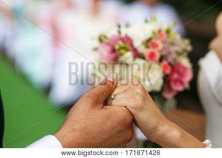 The brides hold hands on the wedding ceremony