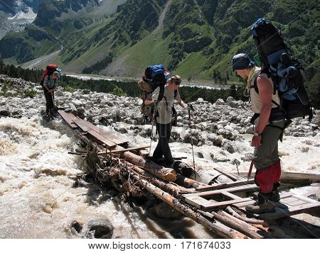 CAUCASUS MOUNTAINS/ RUSSIA - AUGUST 6, 2007: The climbers are crossing a flashy mountain river over the old wooden bridge in the gorge Adyr-Su. Caucasus, Russia.