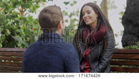 Young man squatting down talking to his girlfriend