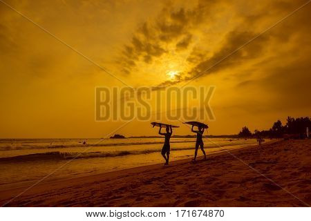 WELIGAMA SRI LANKA - JANUARY 12 2017: Unidentified couple surfing on sunset on Weligama beach on the coast of Indian ocean - is the best surf paradise in Sri Lanka