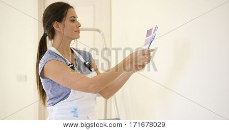 Young decorator deciding on a color of paint