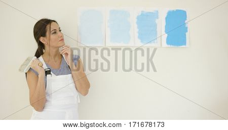 Young woman choosing a new paint for her home