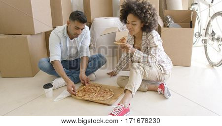 Young African American couple tucking into a pizza