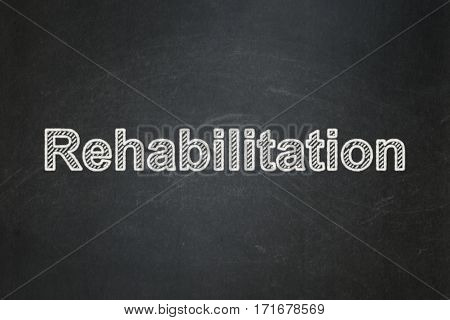 Healthcare concept: text Rehabilitation on Black chalkboard background
