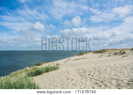 A view of the sand dunes with grass and a fence at Nida, Lithuania.