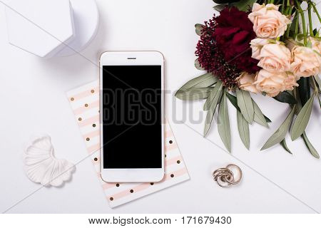 White feminine tabletop flatlay with smartphone mock-up. Home office decor objects.