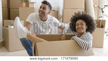 Smiling young woman in a cardboard carton