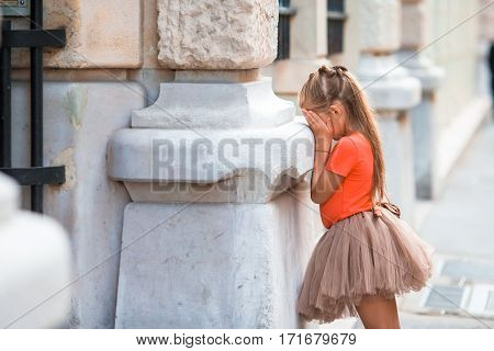 Little girl playing hide and seek on street in Paris outdoors
