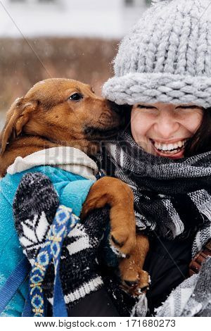 Stylish Hipster Woman Hugging And Smiling Cute Puppy In Snowy Cold Winter Park. Moments Of True Happ