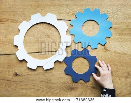 Hand Holding Cog Wheel Sign