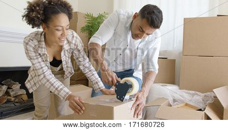 Couple taping boxes as they pack up their home