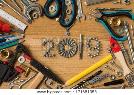 Happy new year 2019 composition with screws nails bolts dowels and tools on wooden background. New year. New year background.