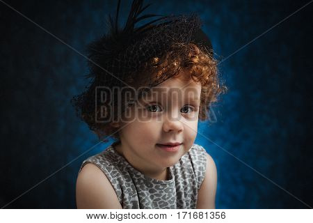 Portrait of cute little girl with hat on her head. Positive expression of shy child.