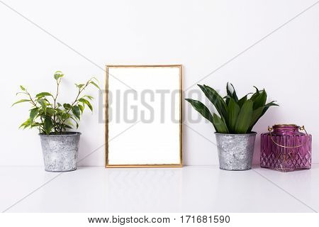 Golden frame mock-up on white wall background, home decor with plants and objects