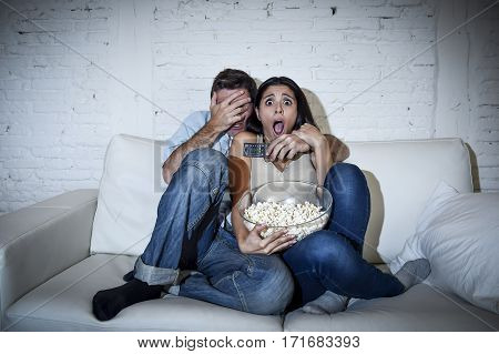 young happy attractive couple having fun at home enjoying watching television horror movie show or thriller film covering eyes together scared in shock at home sofa couch terrified