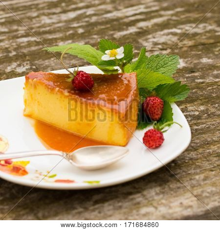 French creme caramel dessert or flan with ingredients at the background Slice of Milk Pudding with mint and strawberries over a wooden table.Panna cotta dessert with caramel sauce Custard pudding