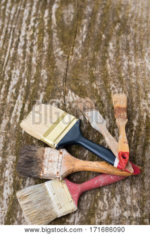 Used brush on wooden background. Repair painting renovation of interior. Accessories for paint . Concept repair. Old dirty dusty painting brush.