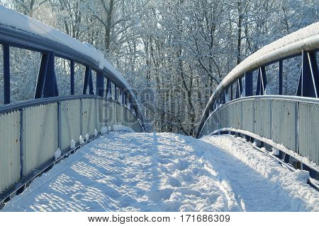 blue footbridge covered with snow in winter