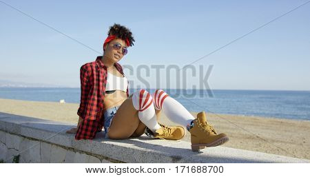 Trendy young woman relaxing on a beachfront wall