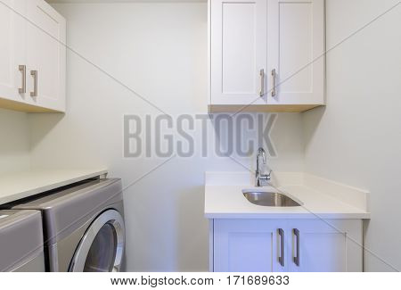 An empty laundry room with cabinet, sink, washer and drier.