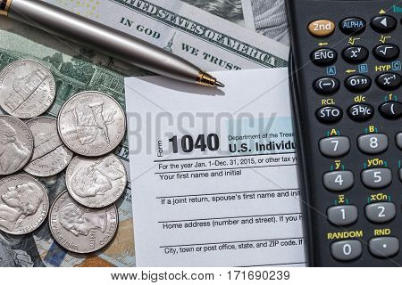 tax form with us dollar bills and coin calculator and pen