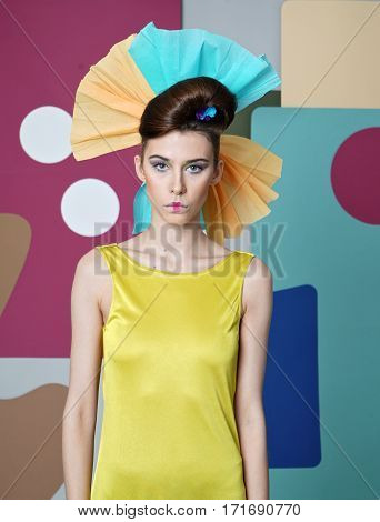 Eccentric outfit: yellow dress with open shoulders, headdress made of colored paper, mouth closed. Shapes: simple geometric forms