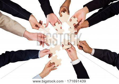 High Angle View Of A Businesspeople Hand Holding Jigsaw Puzzle On White Background