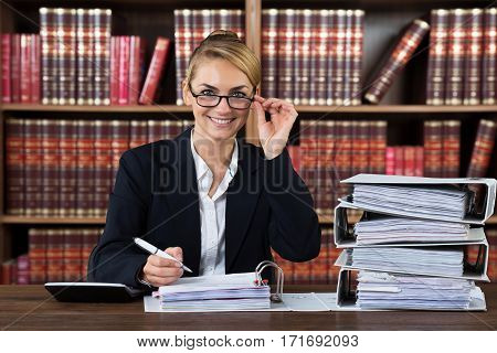 Portrait Of A Successful Female Accountant With Stacked Folders