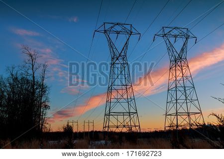 winter landscape transmission line on a background of bright red sunset