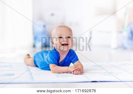 Adorable baby boy learning to crawl and playing with colorful toy in white sunny bedroom. Cute laughing child crawling on a play mat. Nursery interior clothing and toys for little kids.