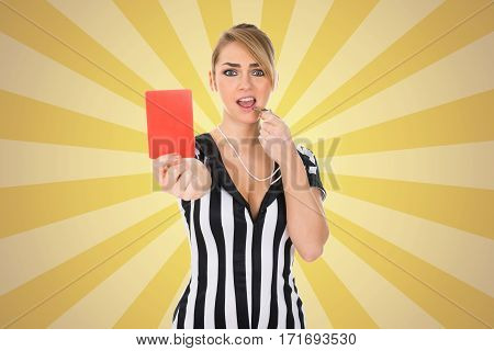 Portrait Of Female Referee Holding Red Card While Blowing Whistle