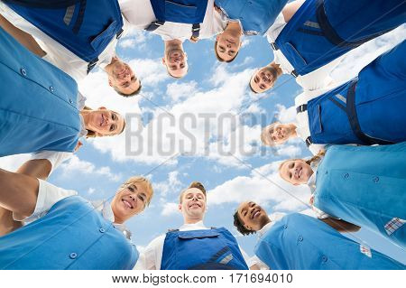 Portrait Of A Confident Janitors Standing In Huddle Against Sky