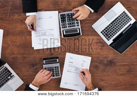 High Angle View Of A Two Accountants Calculating Financial Budget At Office Desk