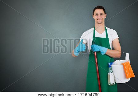 Portrait Of A Male Janitor Holding Cleaning Equipments On Gray Background