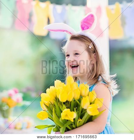 Happy little girl in bunny ears holding tulip flower bouquet. Kids celebrate Easter. Children having fun on Easter egg hunt. Home decoration pastel bunny banner colorful eggs and spring flowers.
