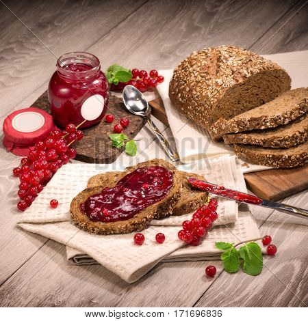 Berry Currant, currant jam, bread, mint leaves, on a light wooden background